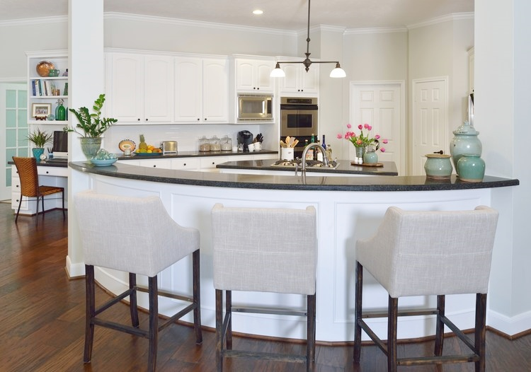 The high bar works well with this kitchen. The curved front and two column on each side would make for an awkward look with a low bar. Carla Aston, Designer | #whitekitchen #kitchenbar #kitchendesign #kitchencountertop