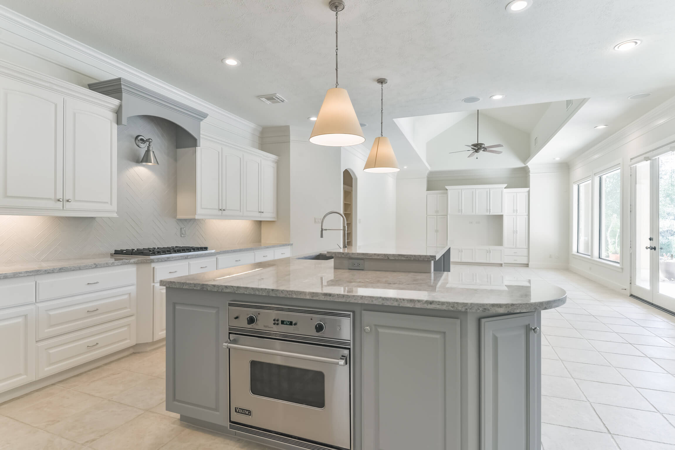 Careful attention was given to the cuts needed for the slabs in this kitchen remodel so we didn't waste any material. Leaving the bar high made more sense here for best use of remodeling dollars. Carla Aston, Designer | #whitekitchen #kitchenbar #kitchendesign #kitchencountertop