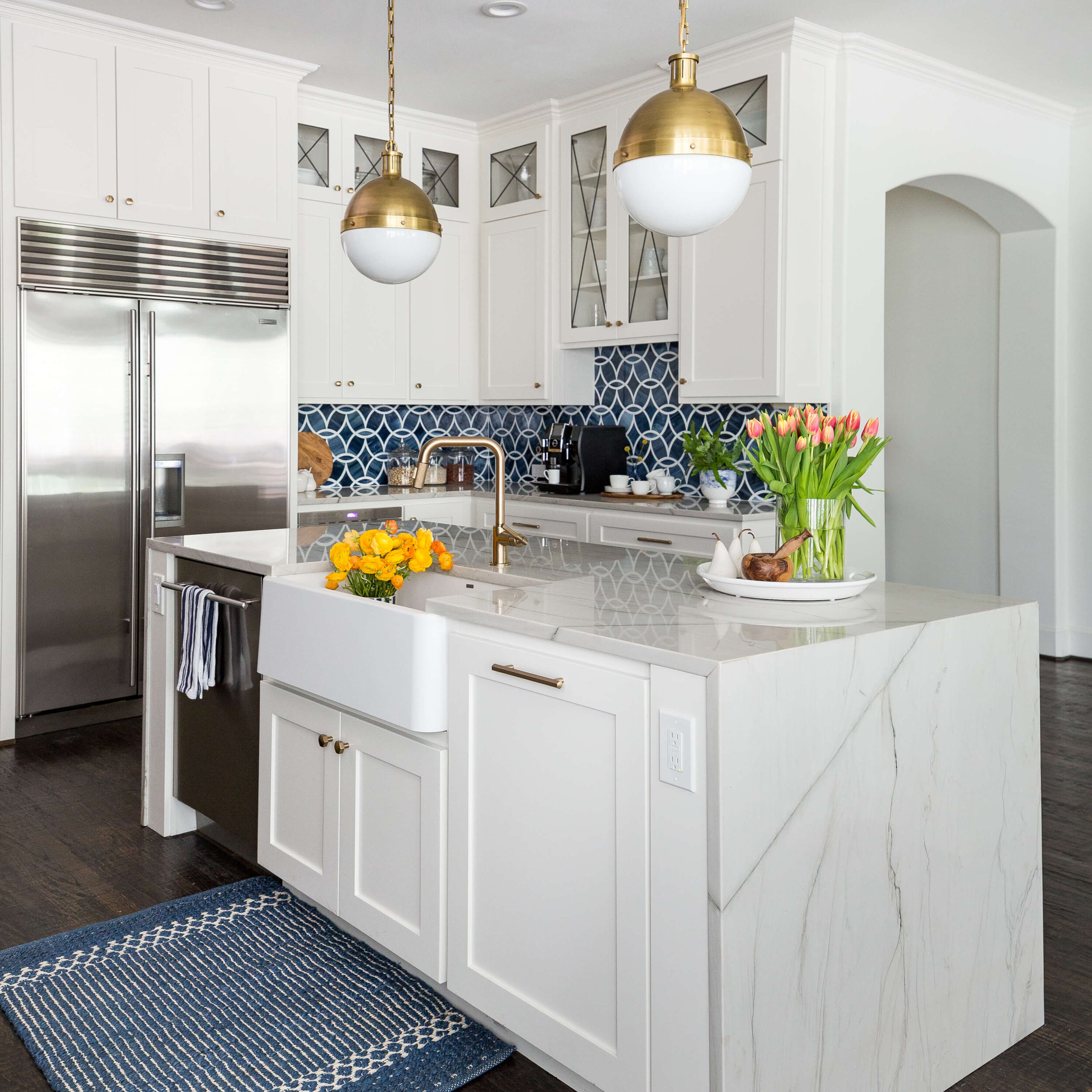 This kitchen has a low bar at the waterfall island. Outlets and switches were designed into the face of the working side, so there would be no interruption on the slab sides. Carla Aston, Designer | Colleen Scott, Photographer | #whitekitchen #kitchenbar #kitchendesign #kitchencountertop