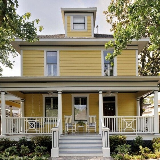 This yellow painted four square house with white trim and porch railings is the most often asked about paint color in my whole portfolio of work. Carla Aston, Designer | Miro Dvorscak, Photographer #yellowpaintcolor #yellowhouse #foursquare #frontporch #paintcolors #choosingpaint