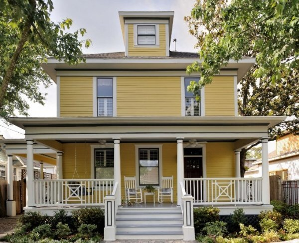 Yellow painted four square house in historic Houston Heights neighborhood. Carla Aston, Designer | Miro Dvorscak, Photographer #yellowpaintcolor #yellowhouse #paintcolors