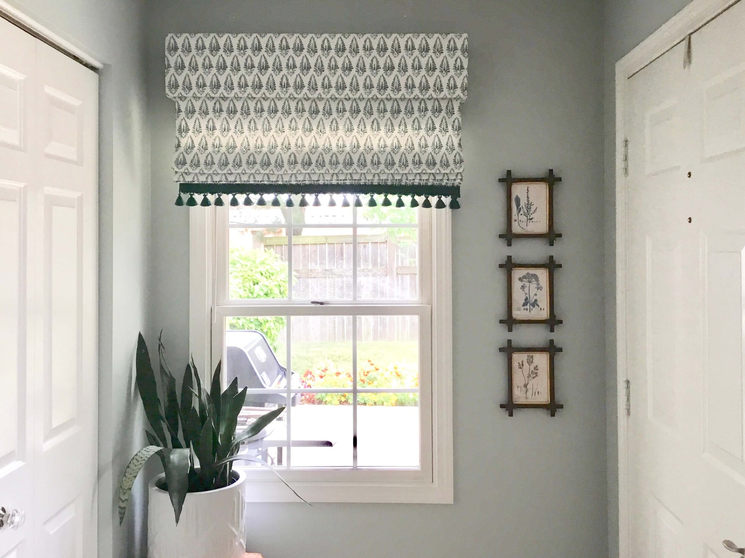 The homeowner did a great job on the Roman shade with the new patterned fabric and trim. It is scaled better for this smaller space and covers the window appropriately. #romanshade #windowtreatment #coastaldecor