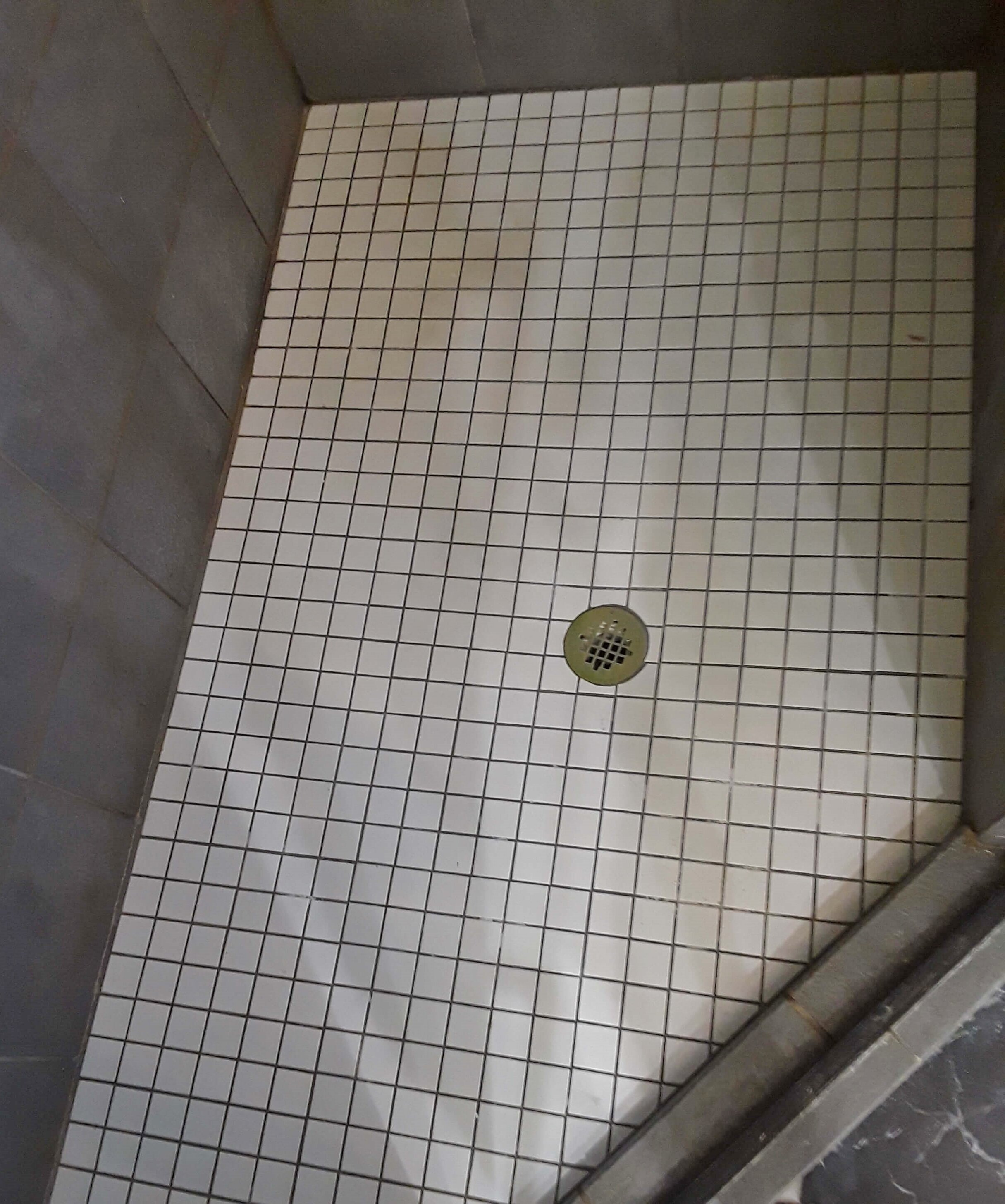 It would be a good idea to change out this shower floor with tile to match the floor of the bathroom to help make this bathroom feel less chopped up and visually flow together. #showerfloor #bathroomshower