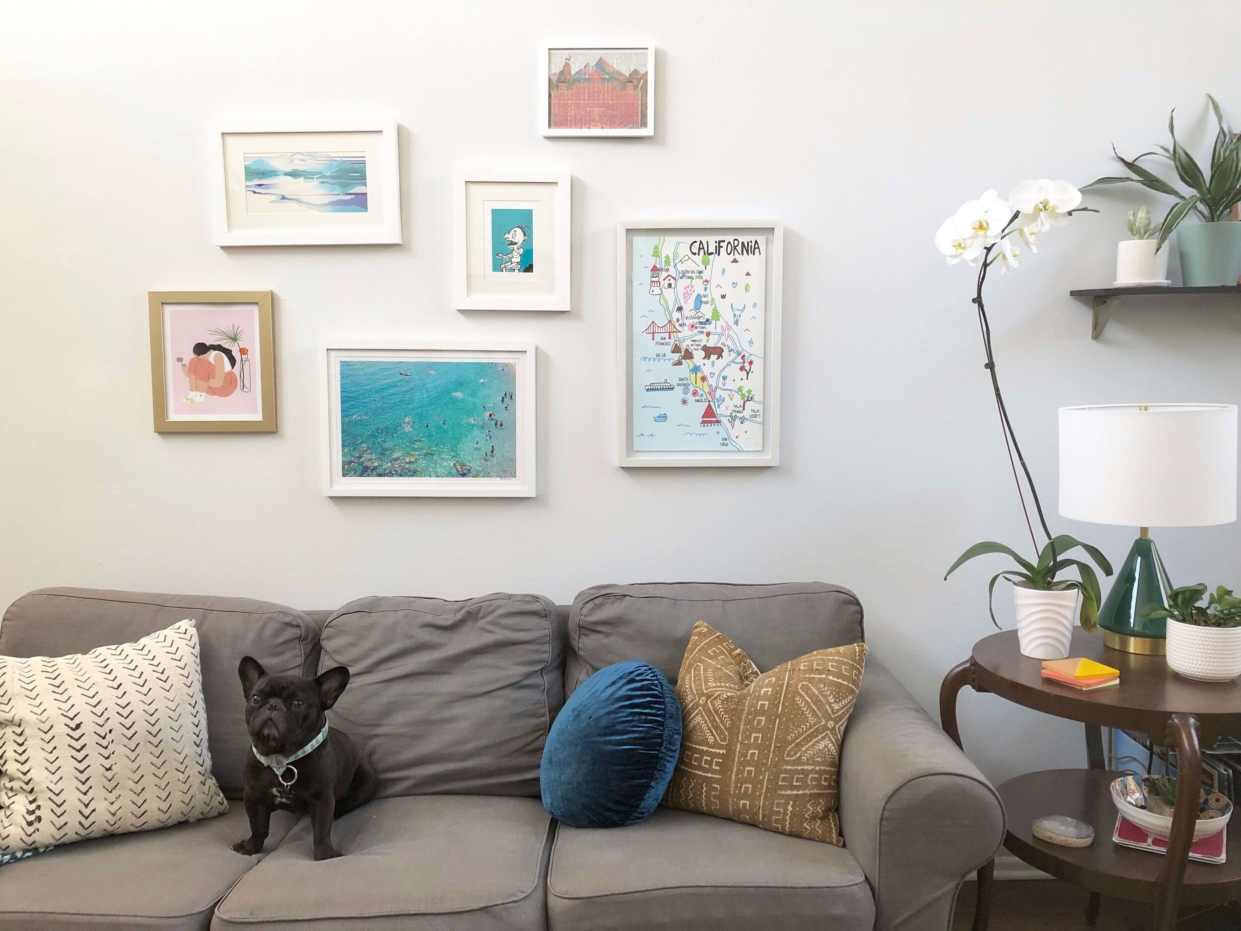Small gallery wall in my daughter's apartment with pieces from her and her roommate combined over an IKEA Ektorp sofa and vintage side table. #modernboho #bohemian
