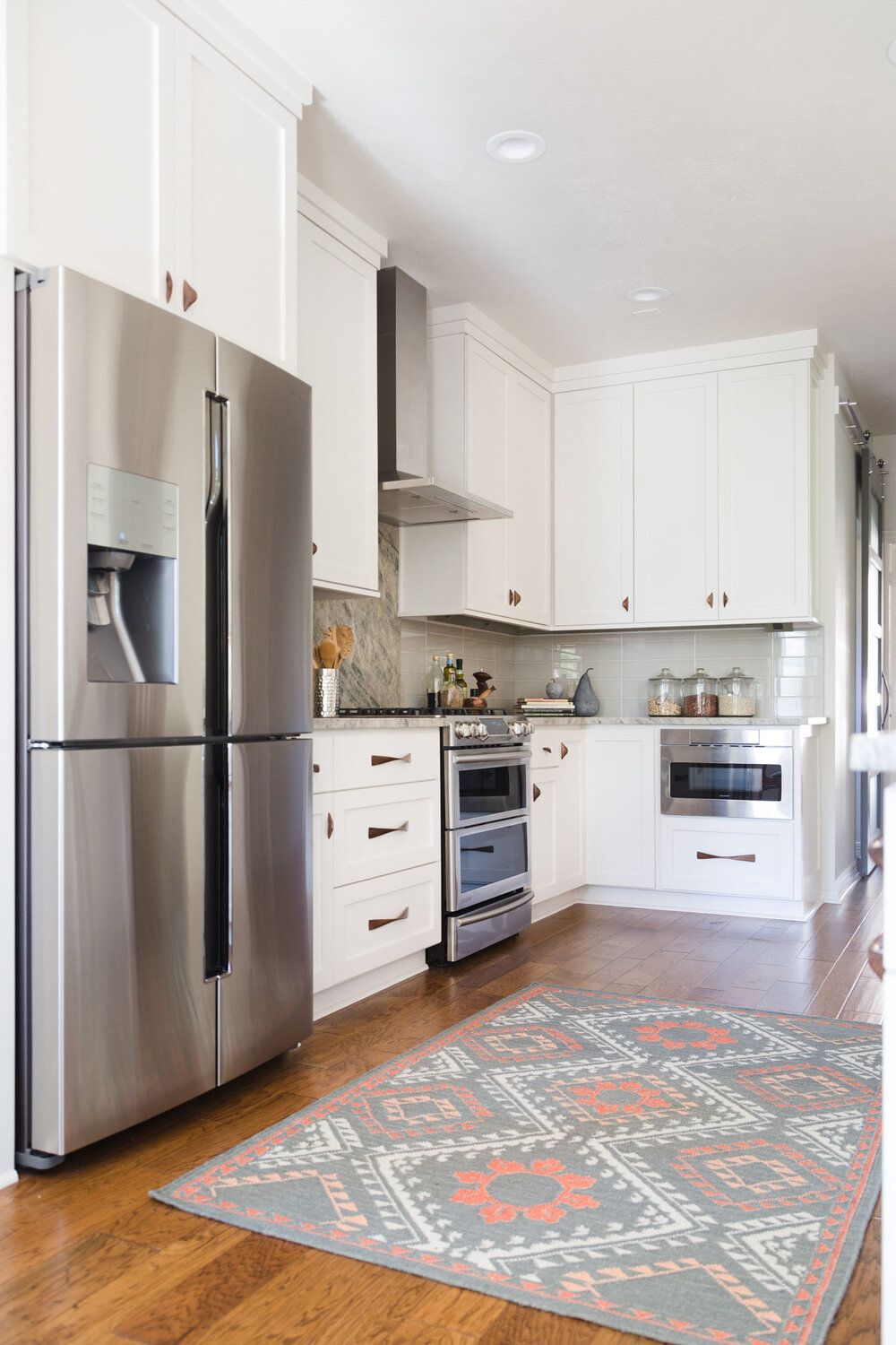 This white kitchen has more personality with the addition of the patterned rug. Designer, Carla Aston | Photographer: Tori Aston #whitekitchen