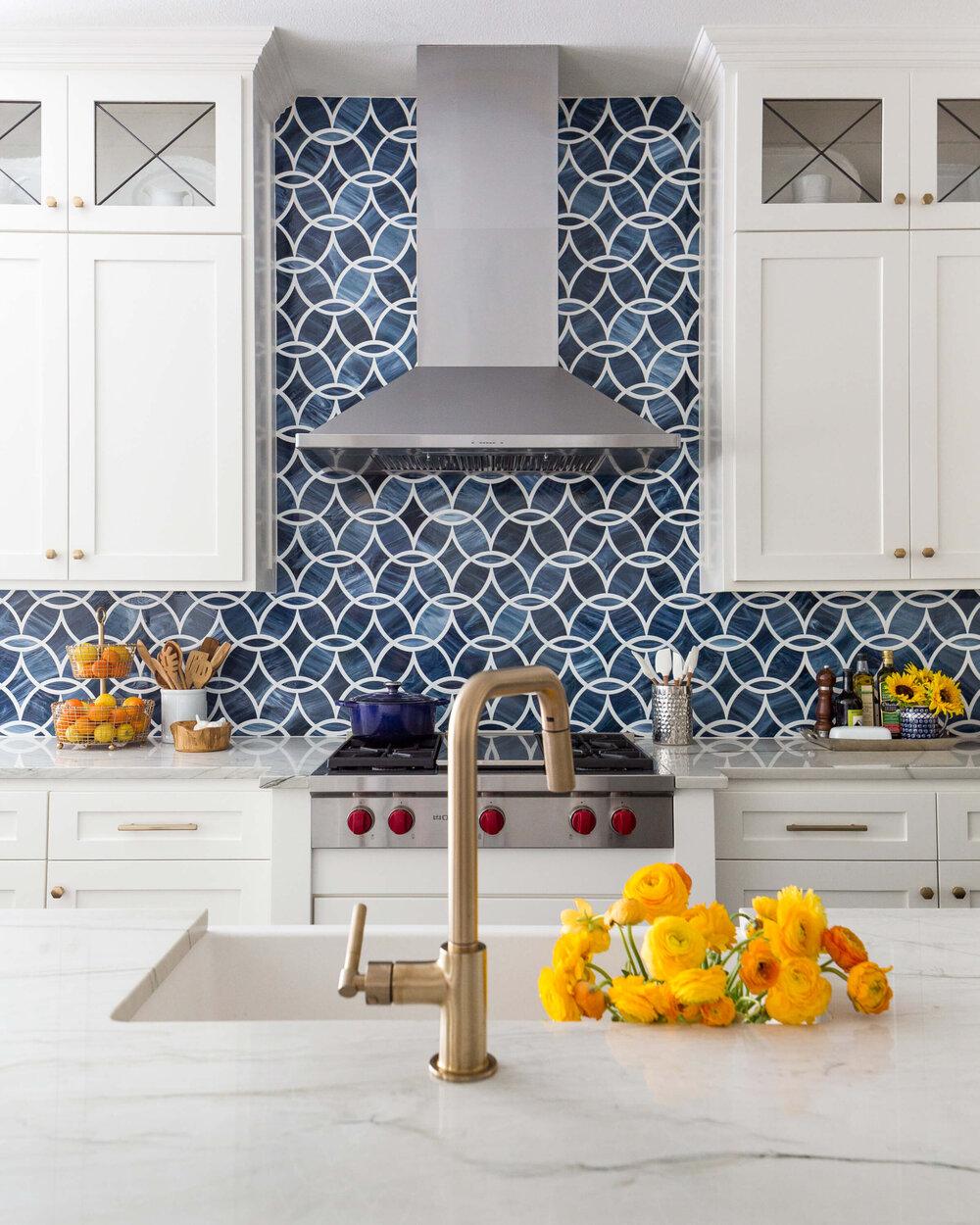A bold blue mosaic tile backsplash makes a big statement in this white kitchen. Designer, Carla Aston | Photographer: Colleen Scott #whitekitchen