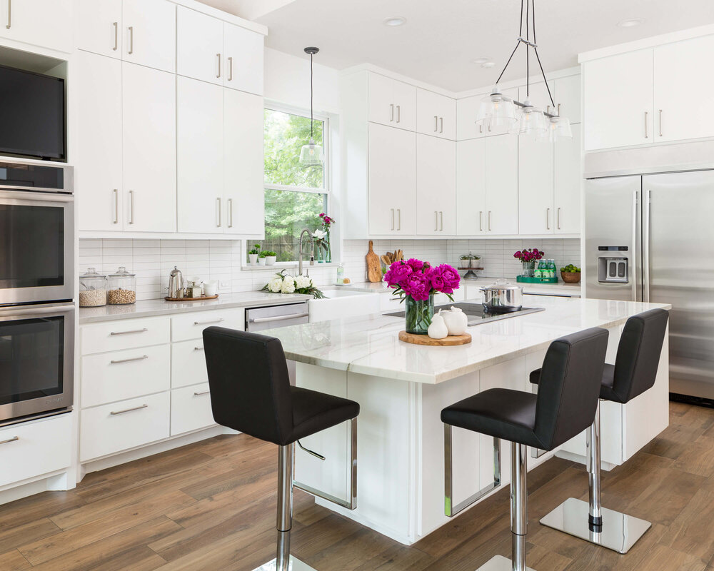 These modern black counterstools give this white kitchen a more contemporary vibe. Designer, Carla Aston | Photographer: Colleen Scott #whitekitchen