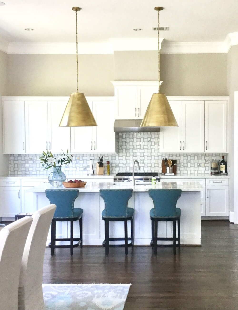Large brass pendants fill the volume of space in this white kitchen with a high ceiling. Carla Aston, Designer #whitekitchen