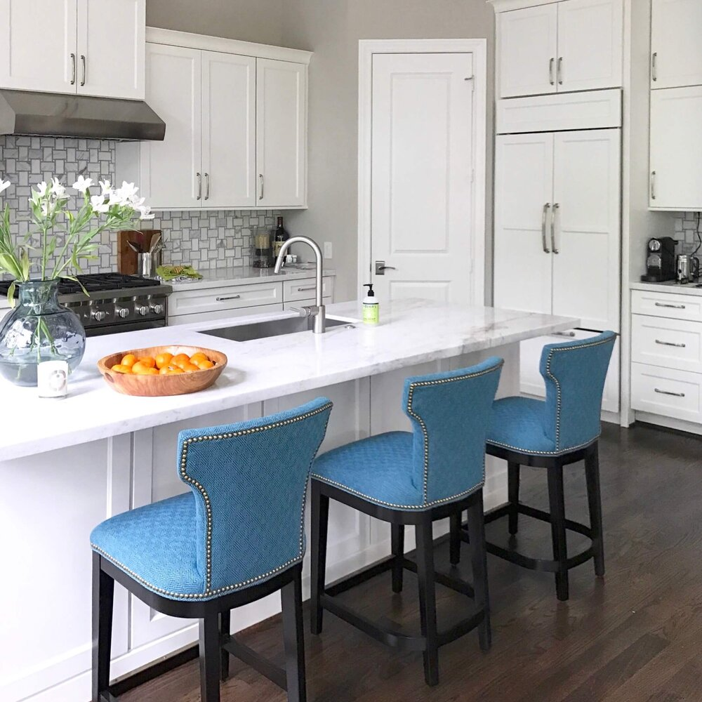 Colorful upholstery on the counterstools add style and interest in this white kitchen. Carla Aston, Designer #whitekitchen
