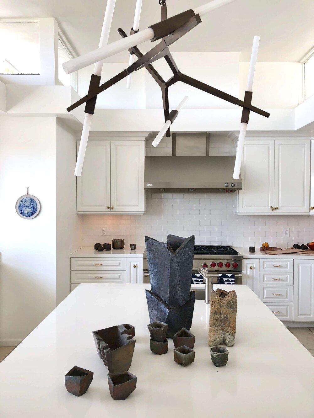 Statement modern lighting works well in this simple white kitchen at Casa Perfect in LA. #whitekitchen