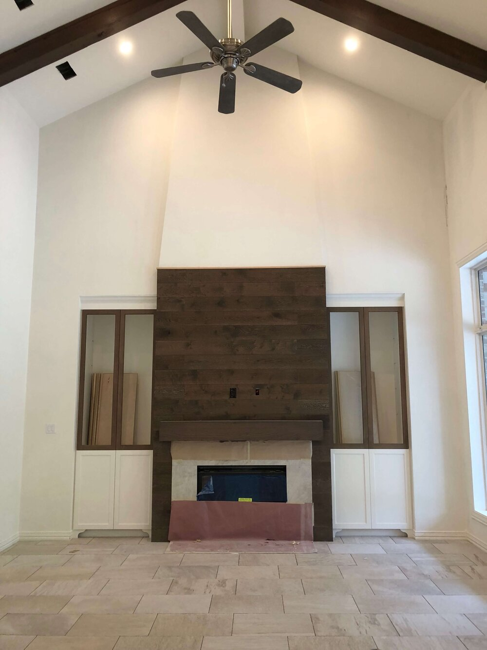 Construction pic - Wood flooring was used to clad this fireplace wall and provide a backdrop for the large tv. A quartzite slab surrounds the firebox. Designer: Carla Aston