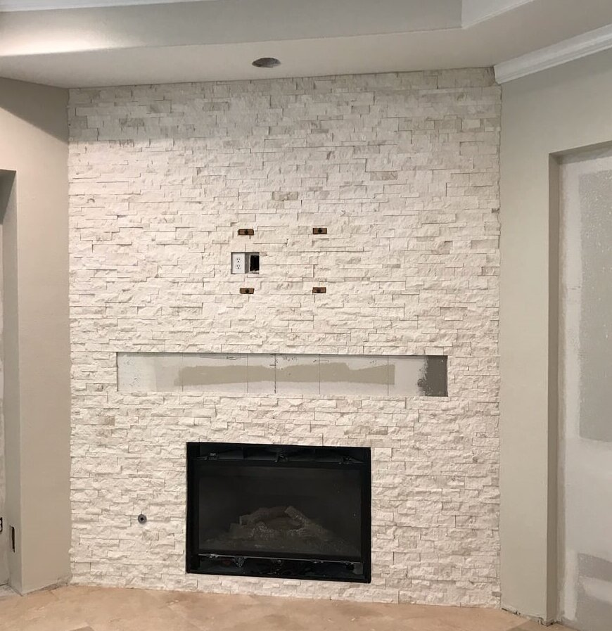 Light, neutral stacked stone covering the wall of the fireplace in this remodel project that was under construction at the time. A rustic mantel will be installed and tv mounted over the fireplace.