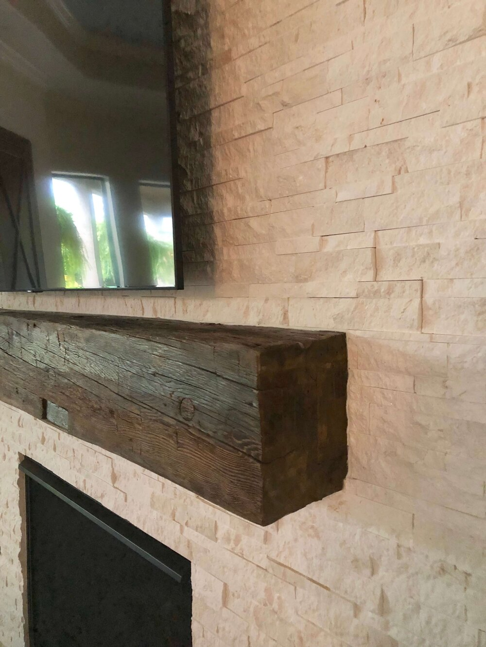 Rustic mantel installed at fireplace wall with light, neutral stacked stone cladding.