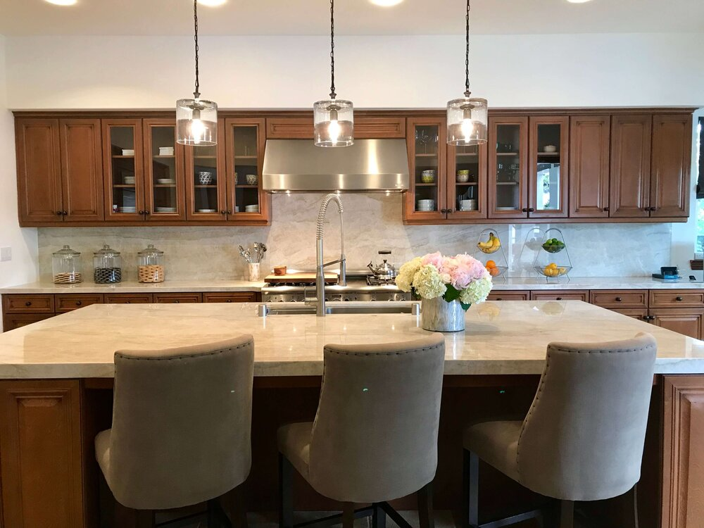 Kitchen with new Taj Mahal countertops and splash that was open to the family room and fireplace wall.
