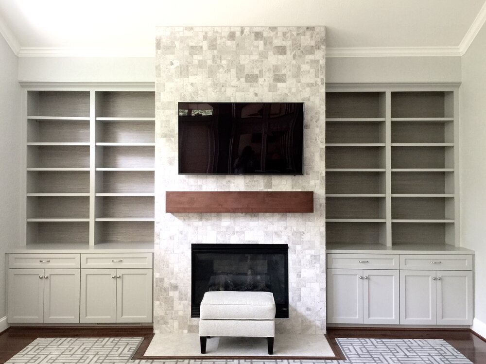 Fireplace wall with natural stone tile cladding fireplace, tv mounted above mantel. Grasscloth installed in backs of bookshelves. Carla Aston, Designer