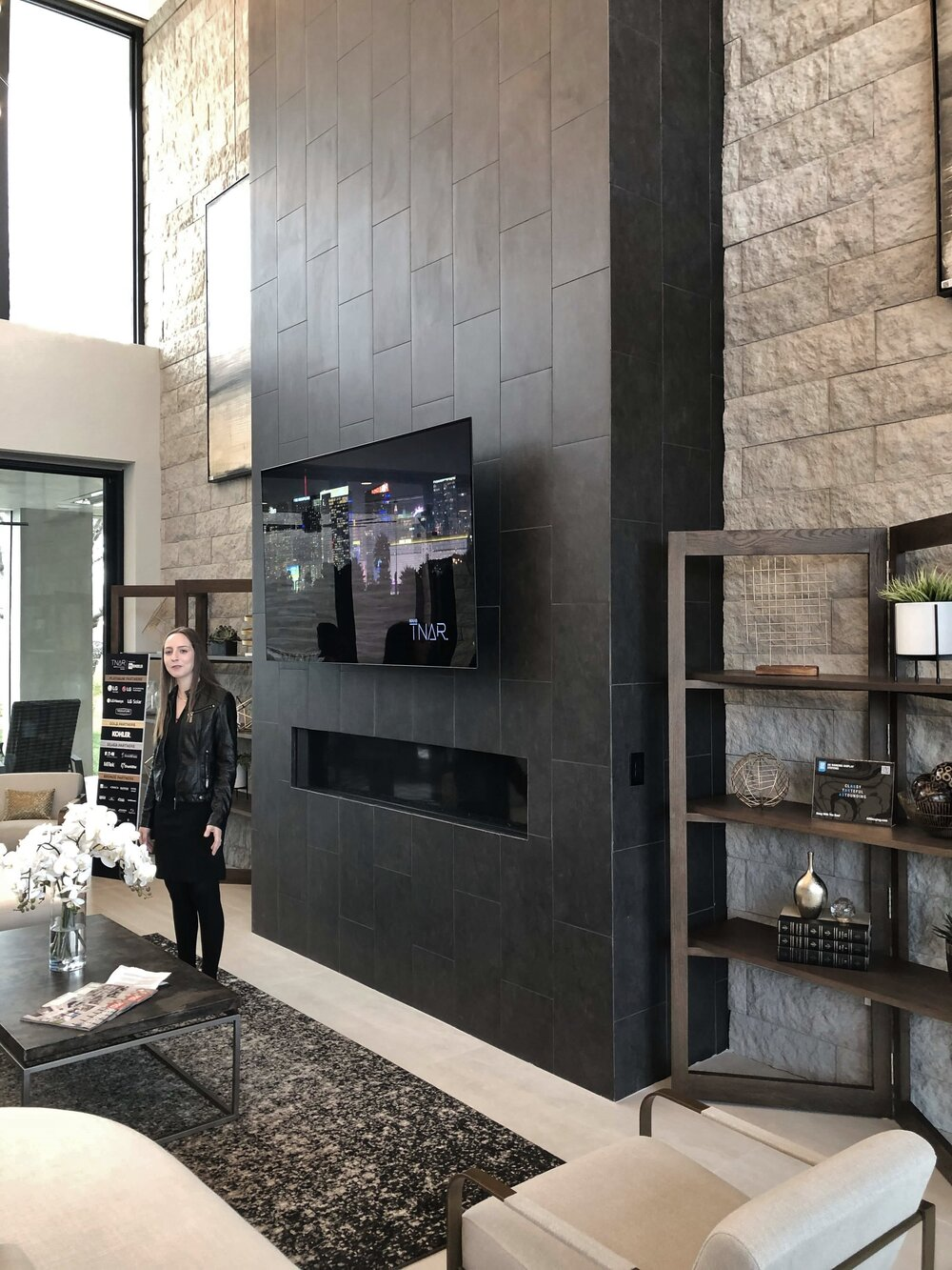 Black tile makes for a strong vertical statement at the two story fireplace in The New American Remodel. TNAR | #remodeling #remodel