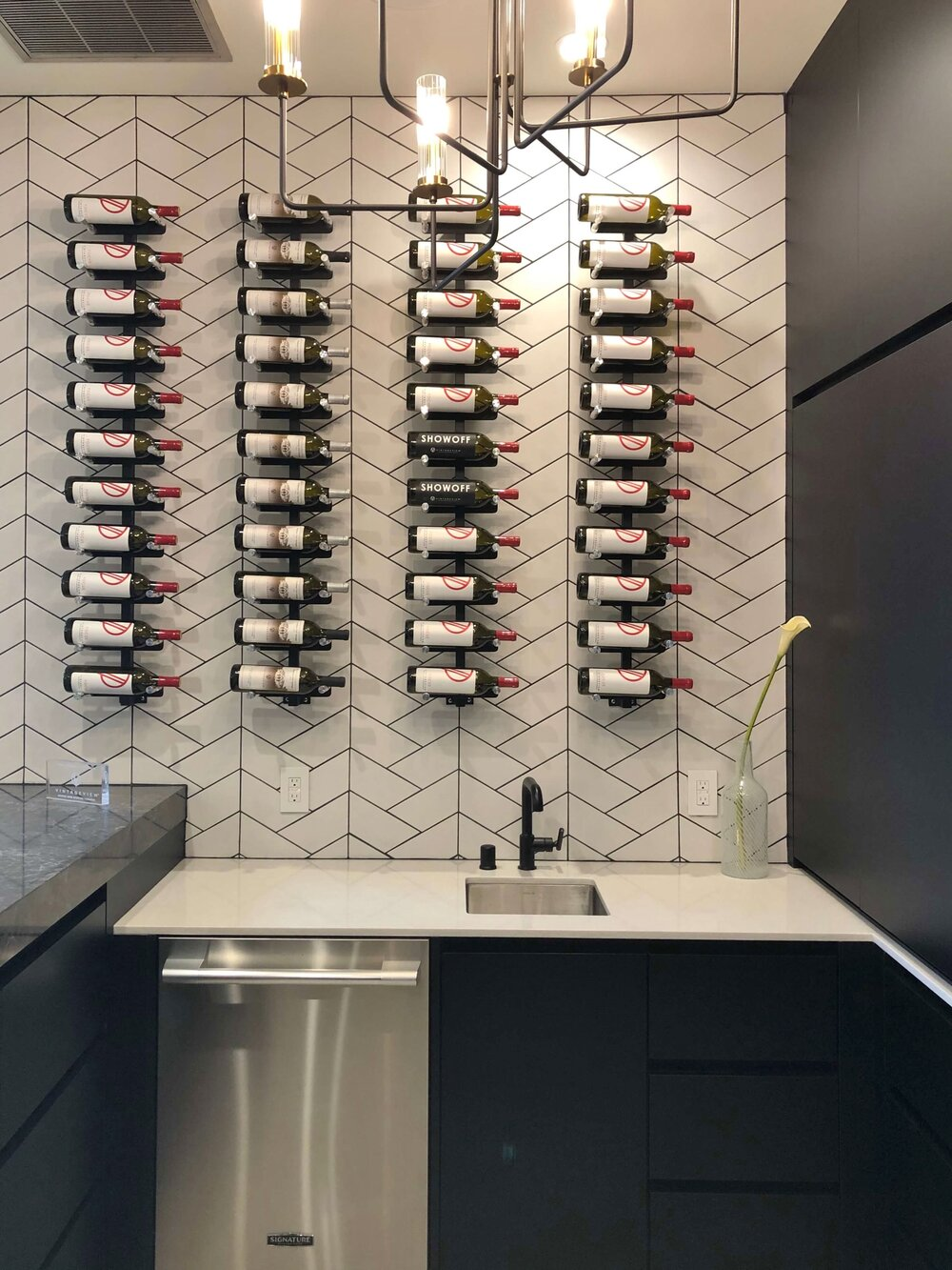 This rack makes for an interesting display of bottles. Great bar space for entertaining. The New American Remodel TNAR | #remodeling #remodel #winebar #winebarideas