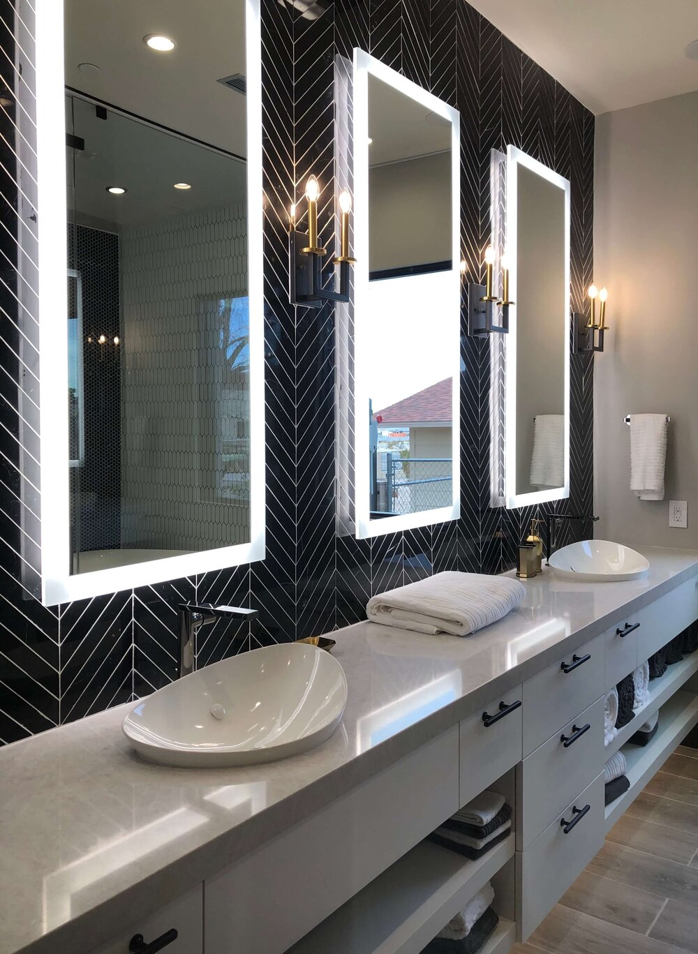 Long vanity with tile wall and floating lit mirrors in The New American Remodel. TNAR | #remodeling #remodel #masterbathideas
