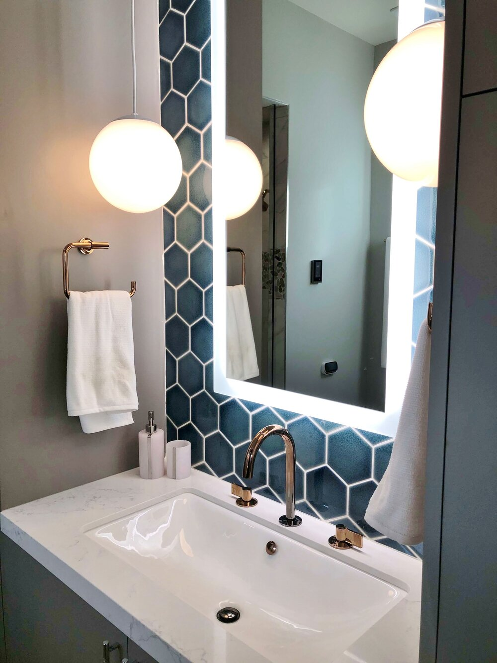Pendant lighting, tiled back wall with floating, lit mirror in the upstairs bathroom. The New American Remodel TNAR | #remodeling #remodel #bathroomdesign