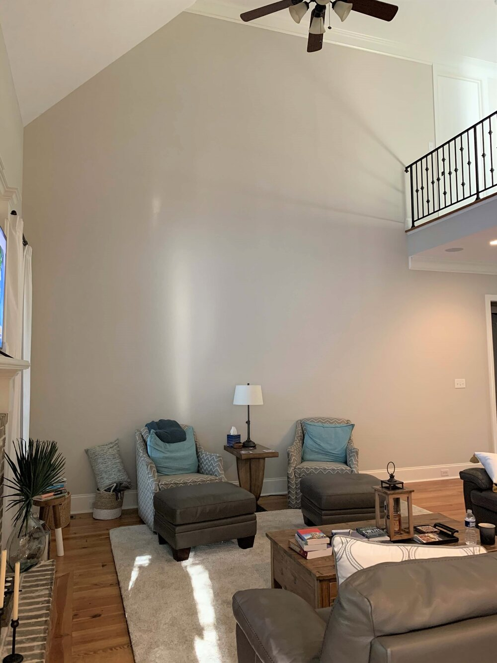 How do you decorate this two story high empty wall in a big living room space?