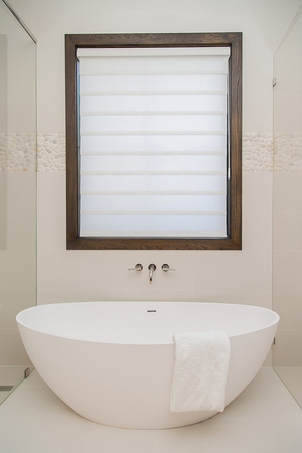 You can see the glass on each side of this tub, with dimensions kept to a minimum to get maximum space for the adjacent shower. Carla Aston, Designer | Tori Aston, Photographer