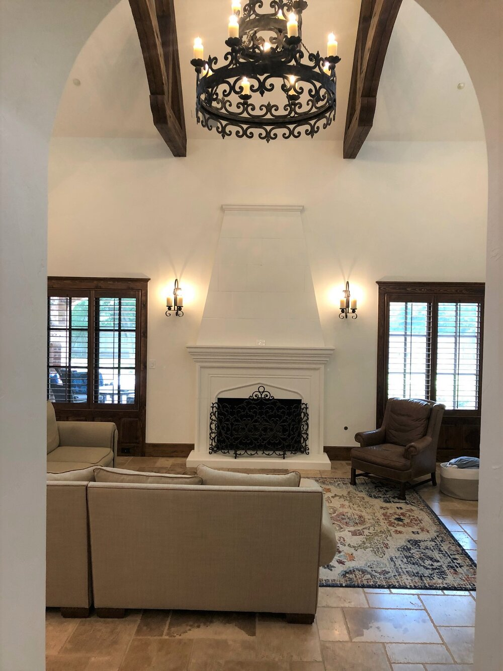 This homeowner wanted to know how to make the fireplace more of a focal point and arrange the furniture to help divide up the space in this Tuscan great room.