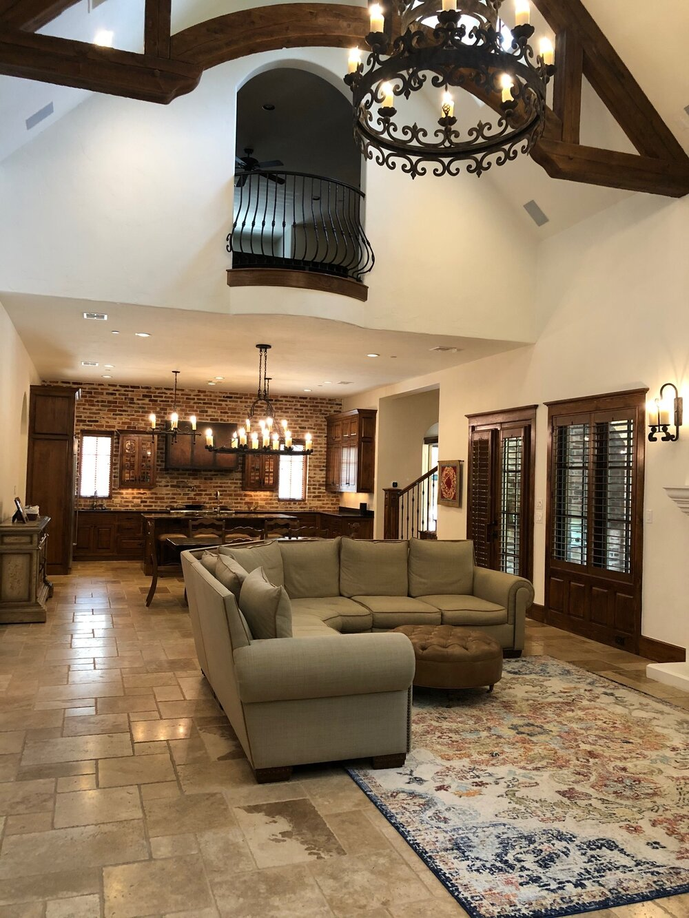 Tuscan style great room with travertine floors, dark doors and trim has been lightened up with a creamy white wall and ceiling paint.