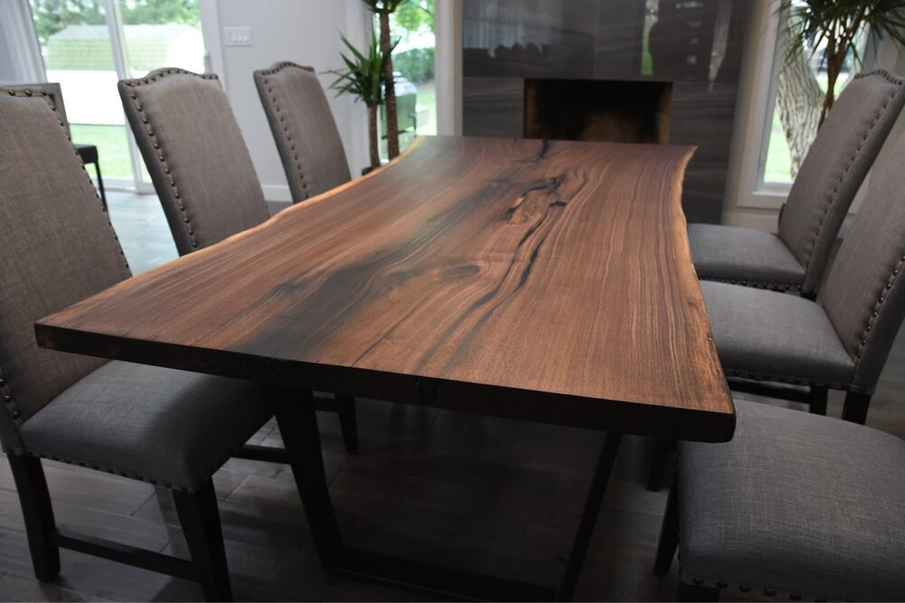 Live edge walnut table with modern base would work beautifully in a Tuscan style home to bring it more up to date.