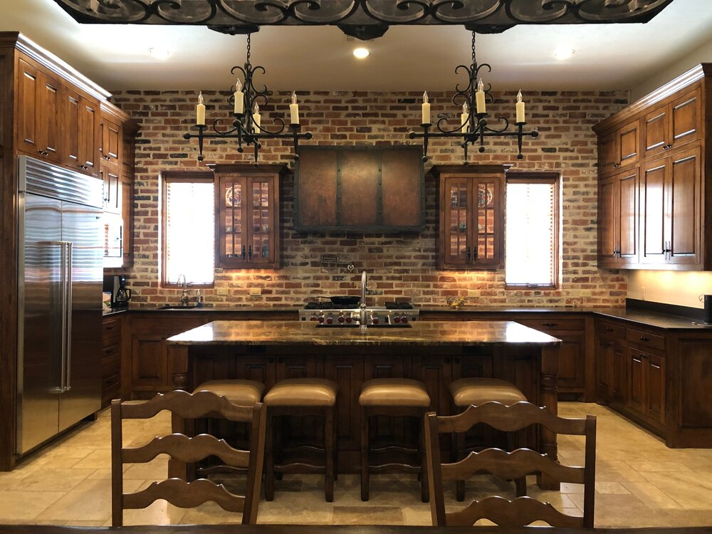 How to lighten and brighten this Tuscan style kitchen with walnut cabinets and a brick wall?