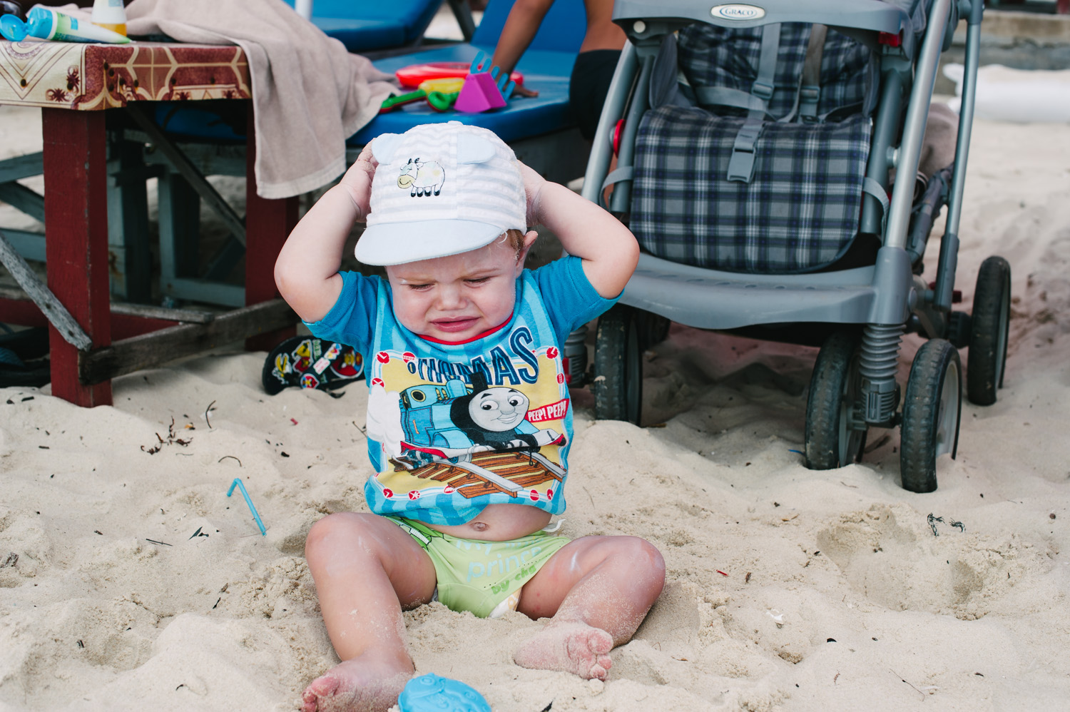Two things: Caleb hates his hat and he's not a fan of the sand...yet.