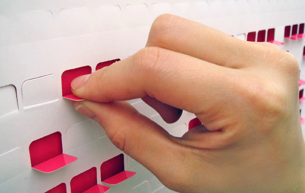 Pull the perforated tabs down to reveal a second level of colour, using them like pixels to compose a message. Project by  Jessica Nebel Design.