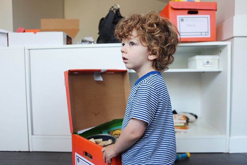 Finley putting things in his cupboard.
