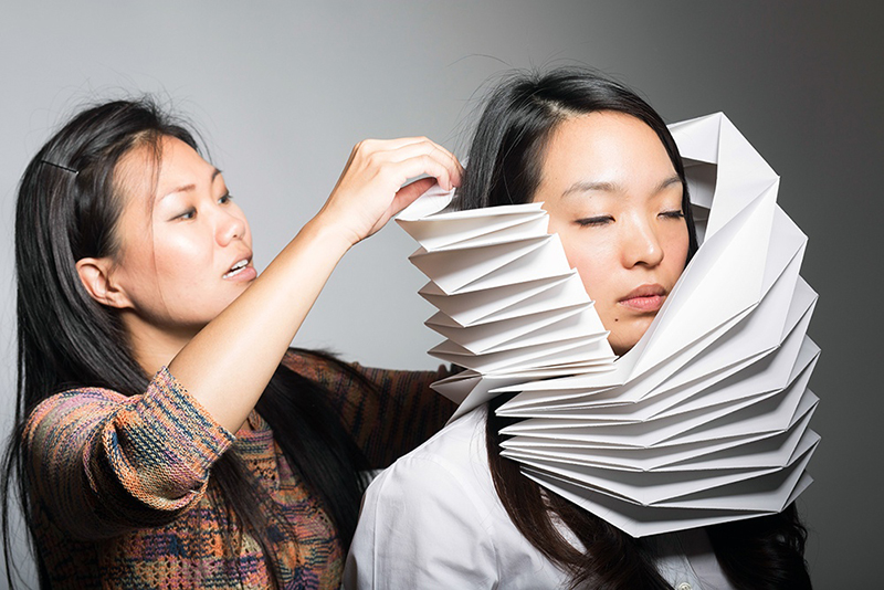 Christine fits the folded paper to model Eunsung Yoon. Photo by Don Toye.