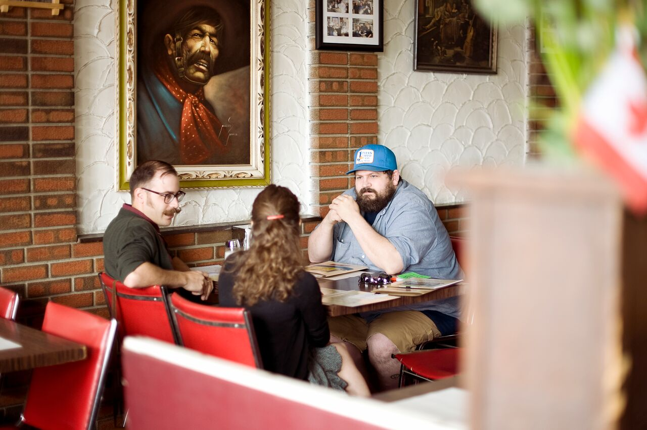 Writer Brendan Harrison and UPPERCASE publisher Janine Vangool have a chat with Aaron Draplin. Calgary, 2012. Photo by Heather Saitz.