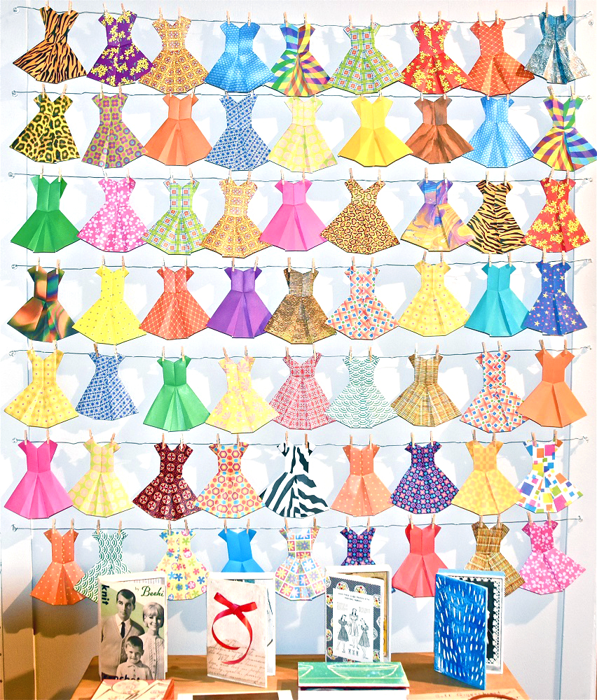 Editor's note: Below these paper dresses, the third card from the left is from the UPPERCASE book  Feed Sacks: The Colourful History of a Frugal Fabric  by Linzee Kull McCray.
