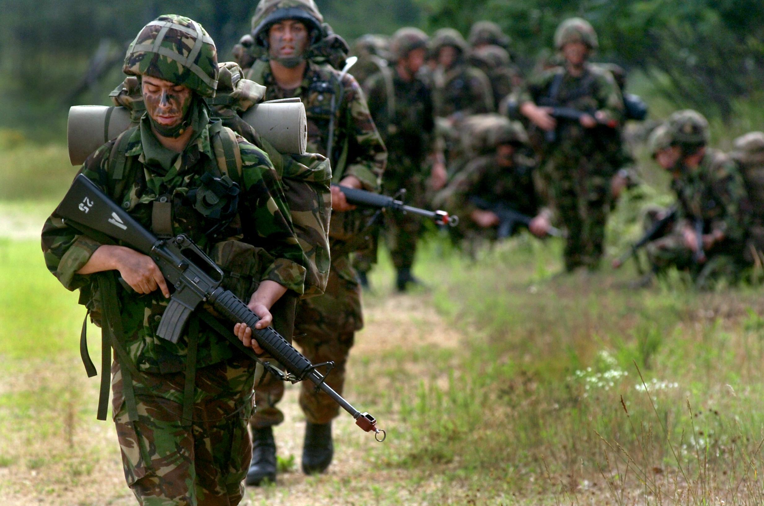 Soldados britânicos marchando. A marcha de soldados é um exemplo típico de população onde ocorre fraturas por estresse. O treinamento intenso com longas marchas e carregando peso extra gera um ambiente propício para isso.