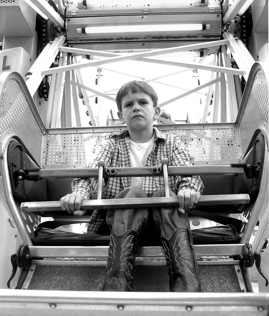 A boy forced to ride the ferris wheel alone.