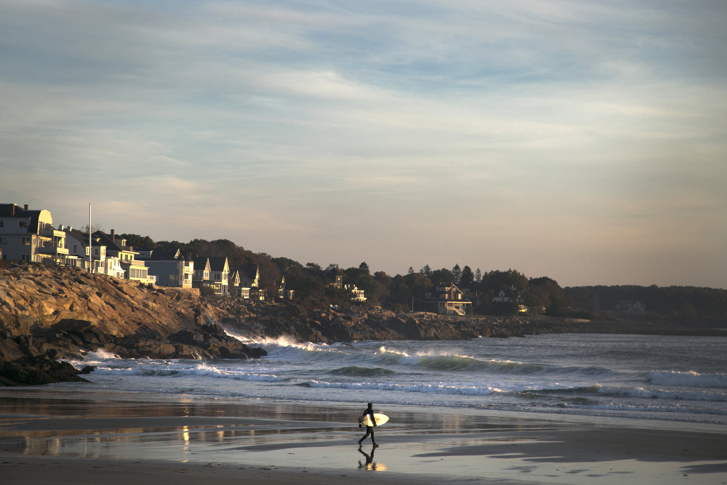 A surfer enters the waters off the coast of York, Maine where wave chasers flock to beaches in mid-October in search of good surfing days.