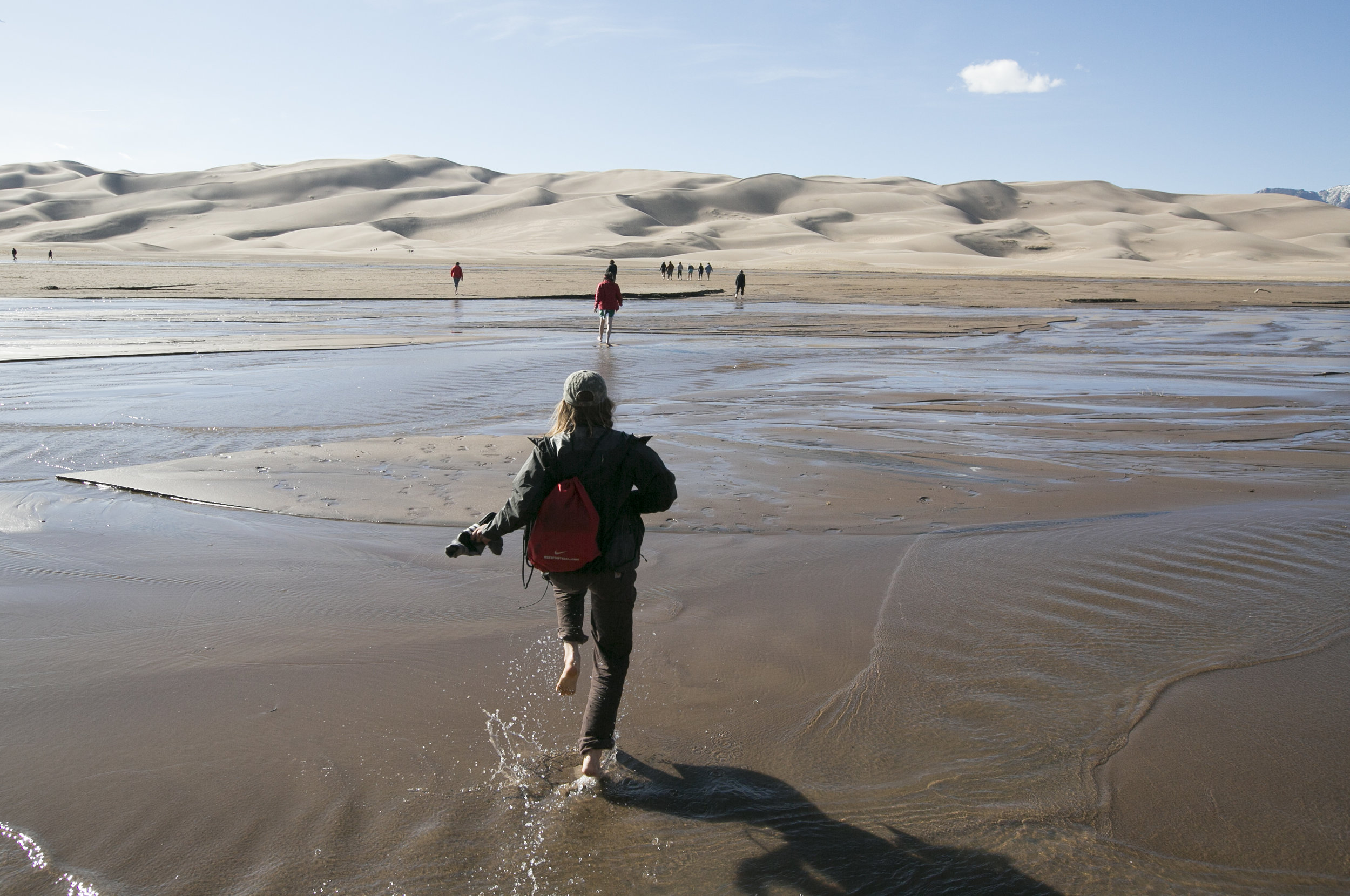 Visitors to Great Sand Dunes National Park run through the streams to get to the sand.