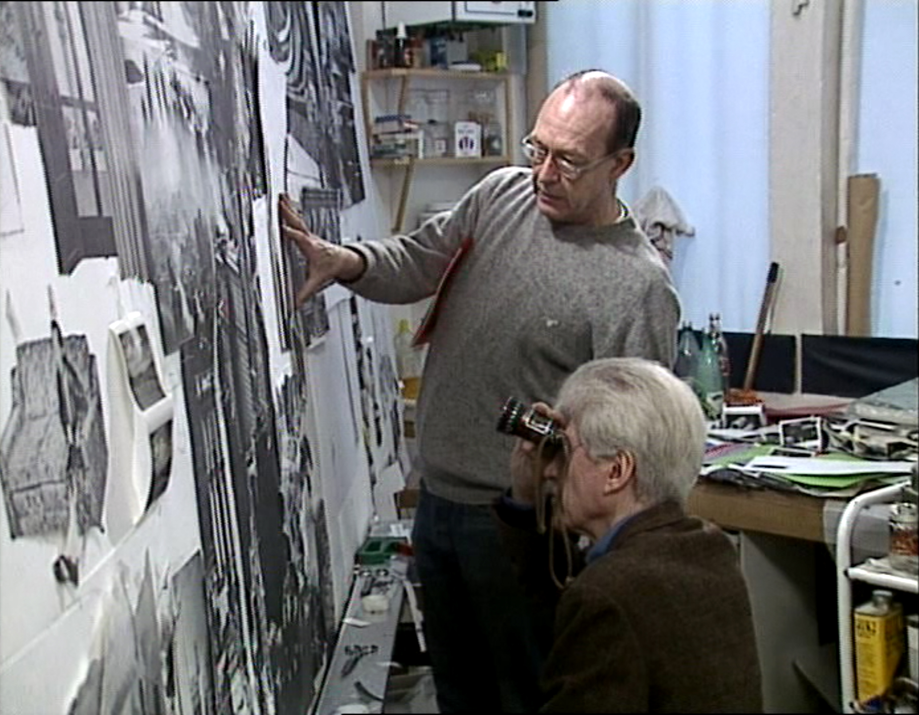Guy Peellaert and Alain Resnais examine details of preparatory sketches for the Gershwin Frieze in Paris, in a still from the documentary short on the making of the Frieze by Gilles Nadeau.