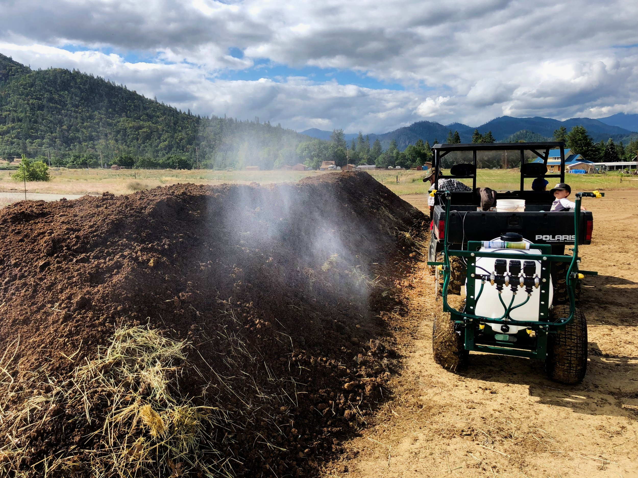 Vineyard manager Adan Cortes, with Andrew Beedy's son Levon along for the ride, sprays BD 507 Valerian onto a compost pile.