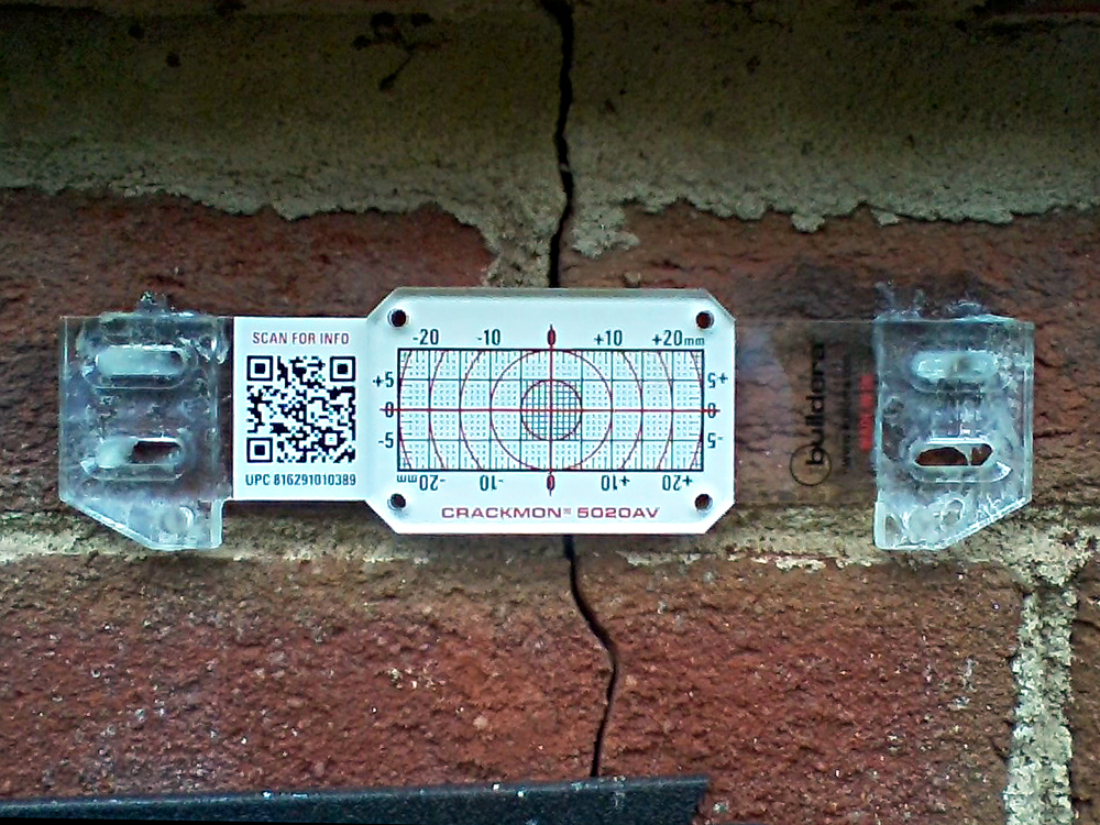 FIGURE 3. Buildera CRACKMON 5020AV crack monitor installed at position No. 1 between crawlspace vent and window along eastern wall. Initial crack width varies between 0.050 and 0.100 inches (1.27 to 2.54 mm). Inside caliper measurement reference: 4.585 inches.