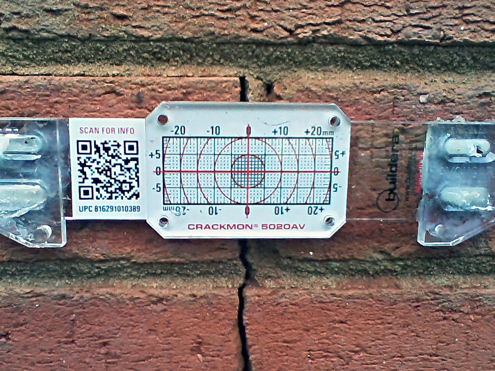 FIGURE 4. Buildera CRACKMON 5020AV crack monitor installed at position No. 2 between finished grade and third brick course along eastern wall. Initial crack width varies between 0.100 and 0.120 inches (2.54 to 3.05 mm). Inside caliper measurement reference: 4.587 inches.