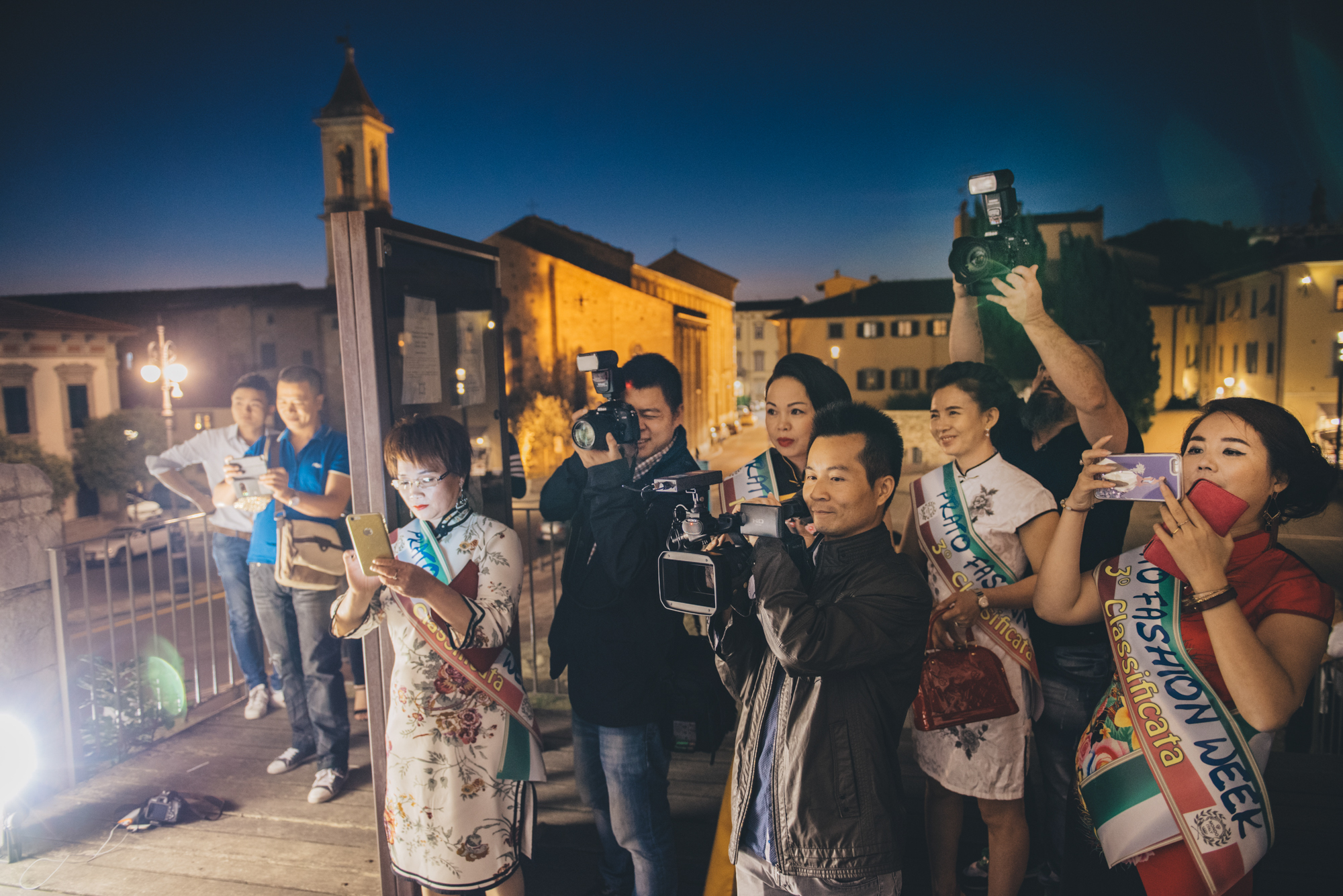 """Prato, July 2016. Models, photographers and reporters attend a photocall at the Castello dell'Imperatore, one of the main landmarks in Central Prato, during """"Prato Fashion Week"""", an event promoting local Chinese fast-fashion businesses."""