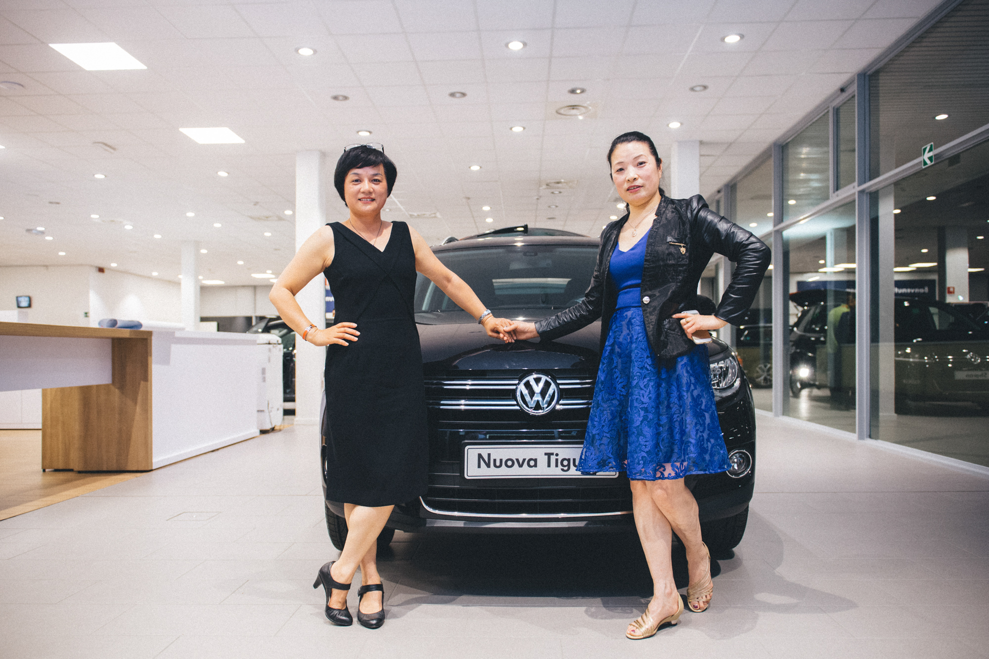 Prato, May 2015. Two women pose for a photo during a promotional event at a local car dealer.