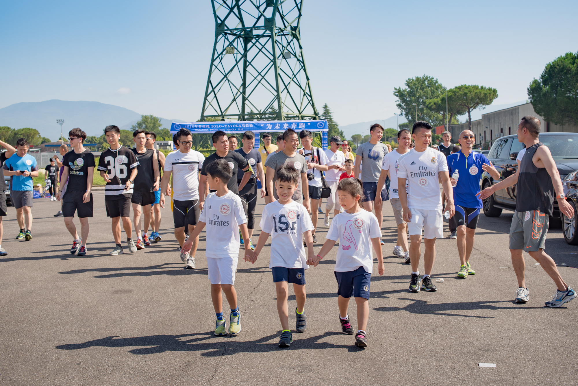 """Prato, June 2016. Runners walk to the start line of the """"Prato-Iolo-Tavola"""" 2016 marathon, organised by local Chinese associations."""