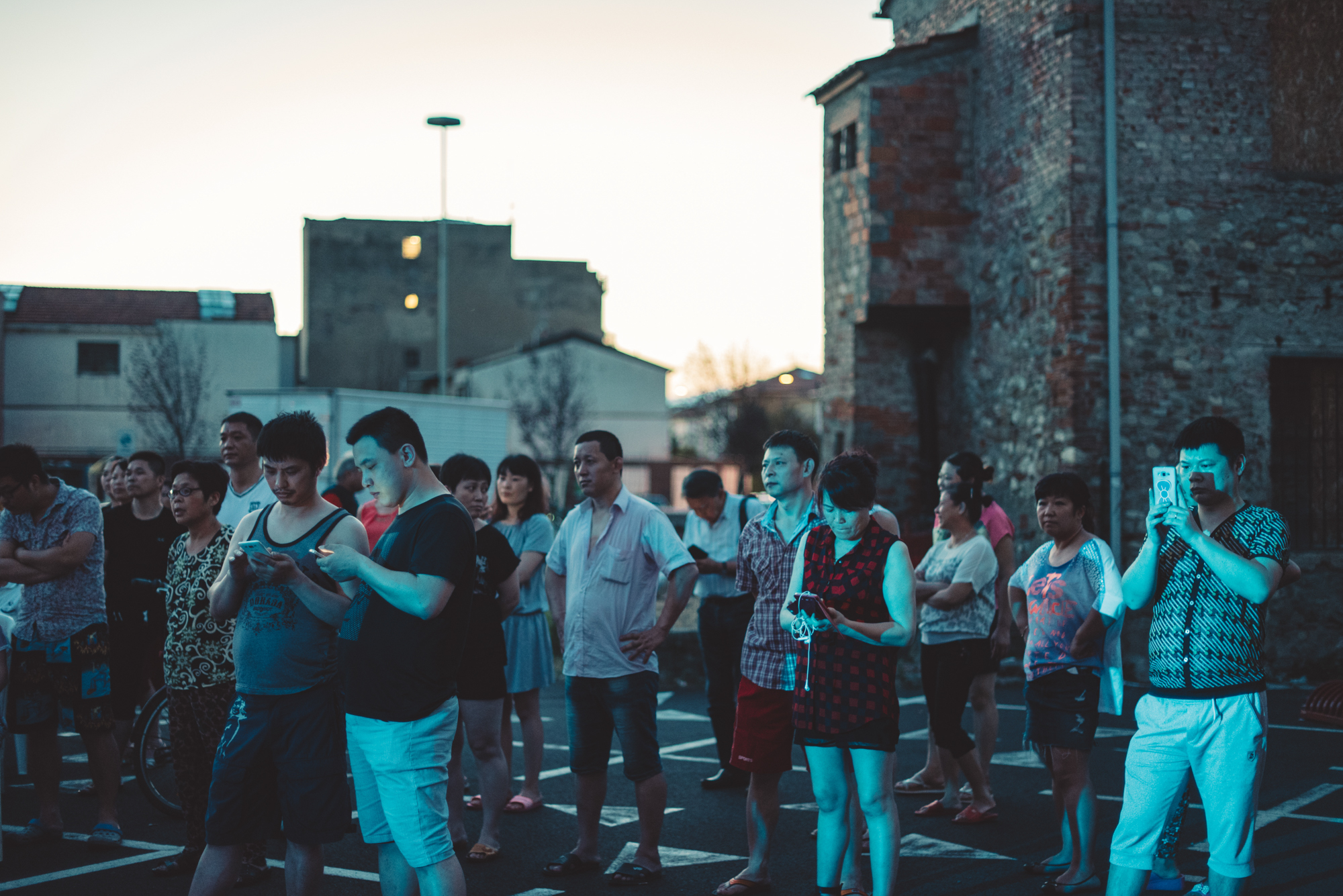Prato, July 2016. Chinese citizens watch and record a show in one of the main squares of the local Chinatown. Smartphones and tables are still the main source of entertainment, communication and contact with friends and relatives in China for the inhabitants of Chinatown.