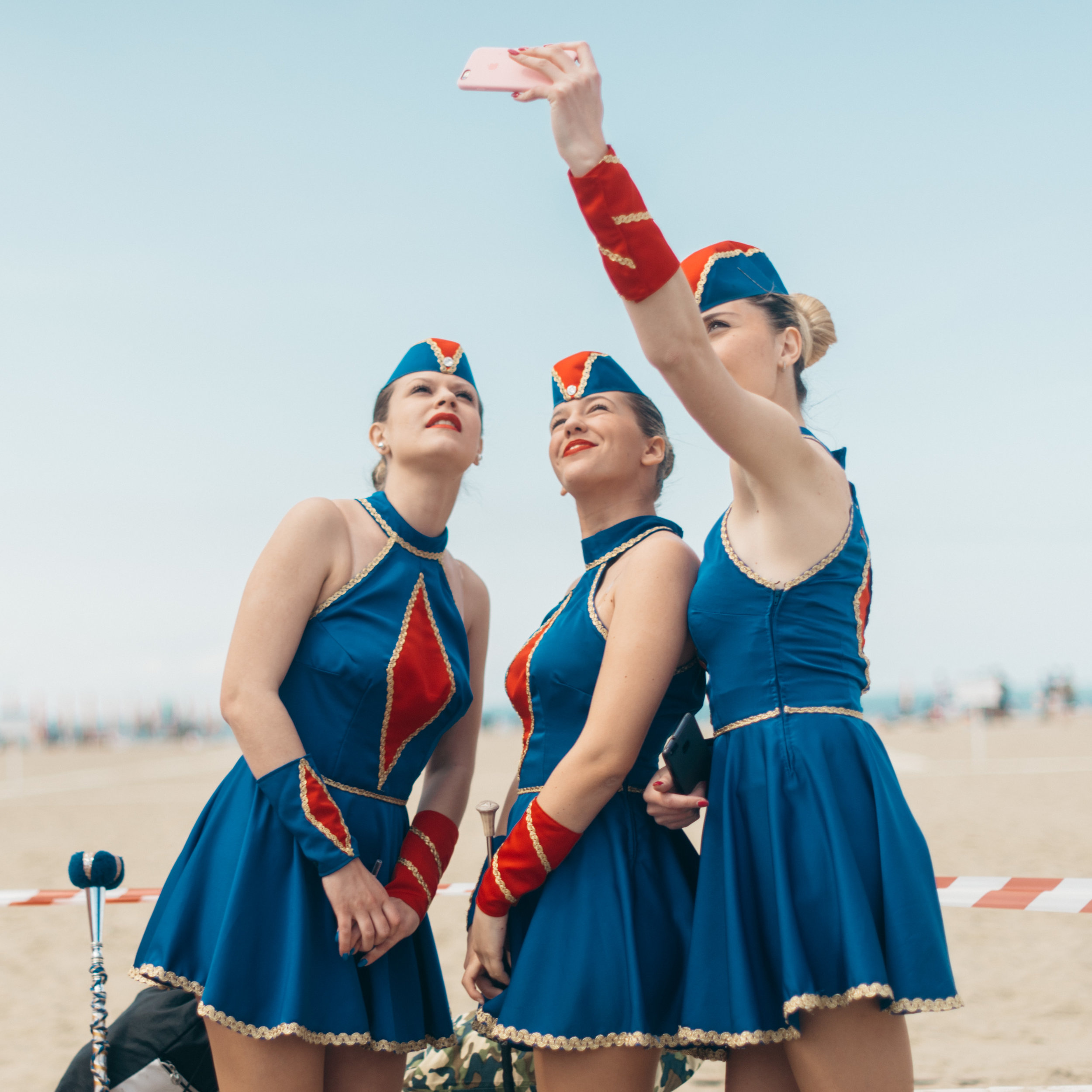 Three girls from the Majorettes di Mentana take a selfie in their uniforms before a competition.