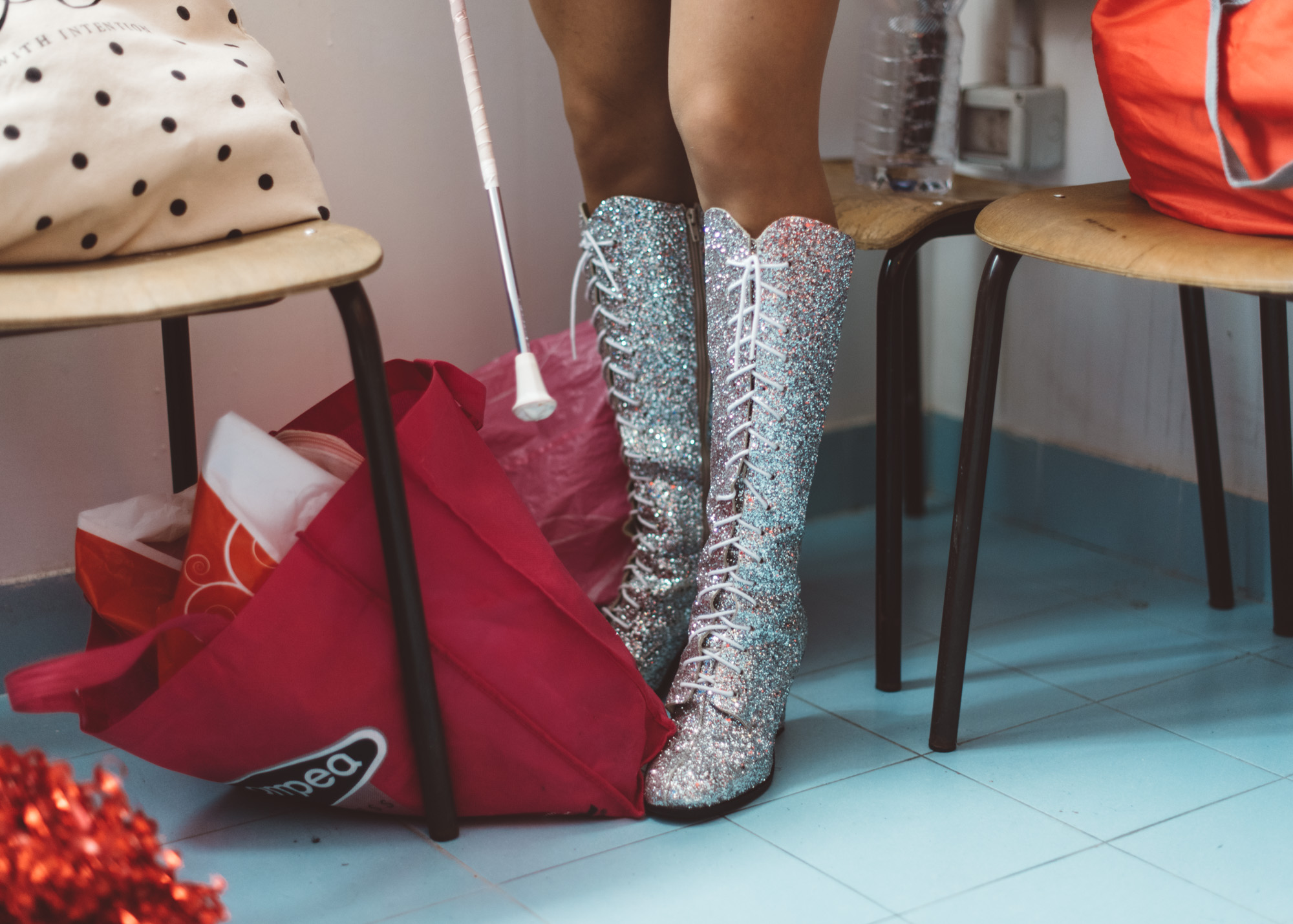 Martina Franca, 2018. A majorette wearing sparkling boots gets changed in the locker rooms of a school gymnasium.