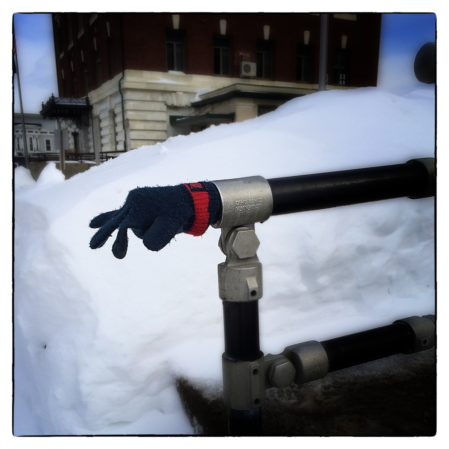 A glove warms the hand rail at the Orleans County Superior Courthouse in Newport, Vt., shot February 18, 2014. The U.S. Courthouse is in the background.